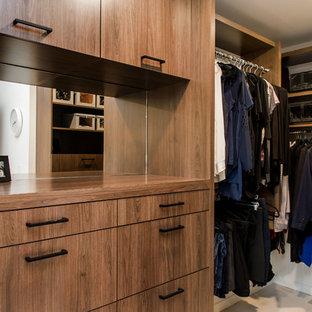 Ejemplo de armario vestidor unisex, vintage, de tamaño medio, con armarios con paneles lisos, puertas de armario de madera oscura y suelo de madera clara