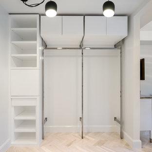 Modelo de armario unisex, tradicional, pequeño, con armarios con paneles lisos, puertas de armario blancas y suelo de travertino