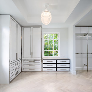 Photo of a large traditional gender neutral standard wardrobe in Miami with flat-panel cabinets, white cabinets and travertine flooring.