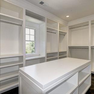 Diseño de armario vestidor unisex, actual, extra grande, con armarios abiertos, puertas de armario blancas, suelo de madera oscura y suelo marrón