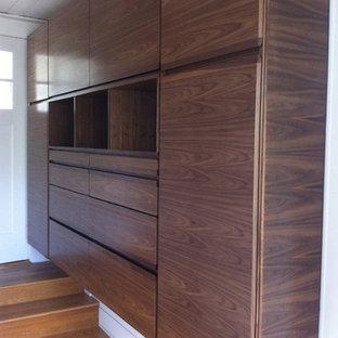 Diseño de vestidor de hombre, vintage, grande, con puertas de armario de madera oscura y suelo de madera clara