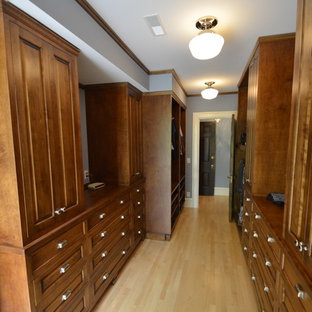 This is an example of a large traditional gender-neutral dressing room in Milwaukee with distressed cabinets, light hardwood floors and recessed-panel cabinets.