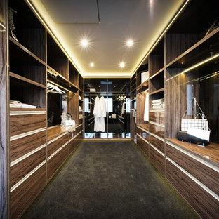 Cette image montre un grand dressing et rangement design avec des portes de placard en bois sombre et un sol noir.