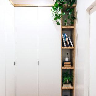 Ispirazione per un piccolo spazio per vestirsi unisex minimal con ante lisce, ante bianche, parquet scuro e pavimento multicolore