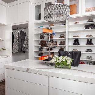 サクラメントの広い女性用コンテンポラリースタイルのおしゃれなウォークインクローゼット (フラットパネル扉のキャビネット、白いキャビネット、クッションフロア、茶色い床) の写真