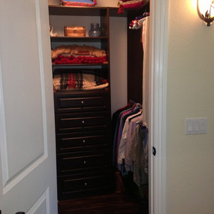 Foto de armario vestidor unisex, tradicional renovado, pequeño, con armarios con paneles empotrados, puertas de armario de madera en tonos medios y suelo de madera oscura