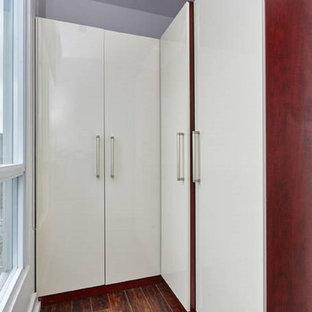 Foto de armario vestidor unisex, actual, de tamaño medio, con armarios con paneles lisos, puertas de armario blancas y suelo de madera oscura