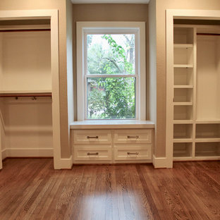 Mid-sized midcentury gender-neutral built-in wardrobe in Houston with shaker cabinets, white cabinets, medium hardwood floors and brown floor.