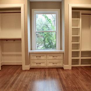 Modelo de armario unisex, retro, de tamaño medio, con armarios estilo shaker, puertas de armario blancas, suelo de madera en tonos medios y suelo marrón