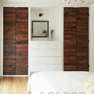 Imagen de vestidor unisex, escandinavo, grande, con armarios con paneles lisos, puertas de armario de madera en tonos medios y suelo de madera clara