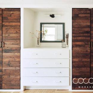 Imagen de vestidor unisex, escandinavo, de tamaño medio, con armarios con paneles lisos, puertas de armario de madera en tonos medios y suelo de madera clara