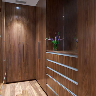 Inspiration for a contemporary gender-neutral light wood floor and beige floor walk-in closet remodel in New York with flat-panel cabinets and dark wood cabinets