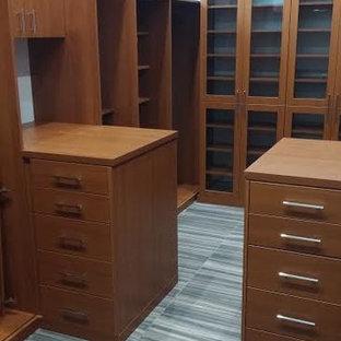 Foto de armario vestidor de hombre, moderno, de tamaño medio, con armarios con paneles lisos, puertas de armario marrones, suelo de pizarra y suelo gris