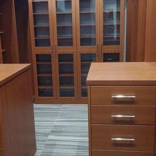 Diseño de armario vestidor de hombre, minimalista, de tamaño medio, con armarios con paneles lisos, puertas de armario marrones, suelo de pizarra y suelo gris