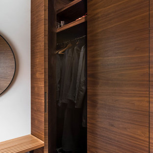 Inspiration for a small midcentury gender-neutral built-in wardrobe in Vancouver with flat-panel cabinets, medium wood cabinets, medium hardwood floors and brown floor.