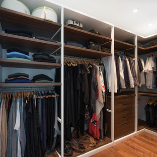 Design ideas for a mid-sized midcentury gender-neutral walk-in wardrobe in Vancouver with open cabinets, dark hardwood floors and brown floor.