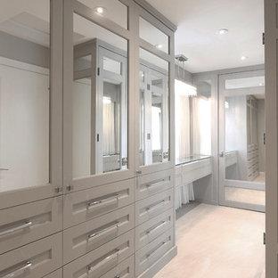 Ejemplo de armario vestidor unisex, actual, grande, con armarios con rebordes decorativos, puertas de armario grises, suelo de baldosas de porcelana y suelo beige