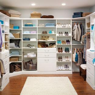 Foto de vestidor unisex, minimalista, grande, con armarios abiertos, puertas de armario blancas y suelo de madera en tonos medios