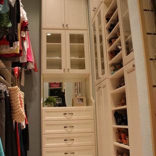 ダラスの広い女性用モダンスタイルのおしゃれなウォークインクローゼット (白いキャビネット、リノリウムの床、落し込みパネル扉のキャビネット) の写真