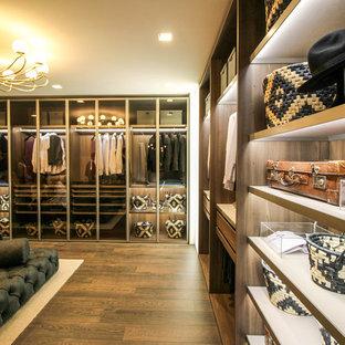 Ejemplo de vestidor moderno, extra grande, con armarios tipo vitrina, puertas de armario de madera oscura y suelo de madera en tonos medios