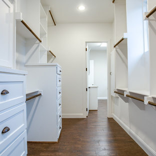 Inspiration for a large country gender-neutral medium tone wood floor and brown floor walk-in closet remodel in Dallas with shaker cabinets and white cabinets