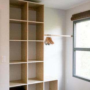 Ispirazione per un piccolo spazio per vestirsi minimalista con nessun'anta, ante in legno chiaro, pavimento in cemento e pavimento grigio