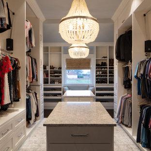 Diseño de armario vestidor unisex, de estilo de casa de campo, grande, con armarios con paneles empotrados, puertas de armario amarillas, suelo de baldosas de porcelana y suelo gris