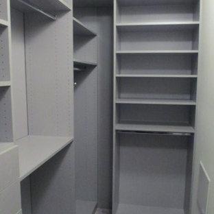 Ejemplo de armario vestidor unisex, minimalista, pequeño, con armarios con paneles lisos, puertas de armario grises, moqueta y suelo beige