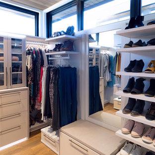 Modelo de vestidor de mujer, moderno, grande, con armarios con paneles lisos, puertas de armario de madera clara y suelo de madera en tonos medios
