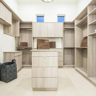 Imagen de armario vestidor unisex, moderno, extra grande, con armarios con paneles lisos, puertas de armario de madera clara, suelo de baldosas de porcelana y suelo beige