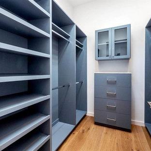 Cette image montre un dressing minimaliste de taille moyenne et neutre avec un placard à porte plane, des portes de placard grises, un sol en bois brun et un sol marron.
