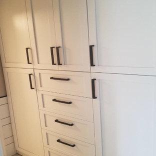 Diseño de armario vestidor unisex, moderno, de tamaño medio, con armarios con paneles empotrados, puertas de armario blancas, suelo de baldosas de porcelana y suelo blanco