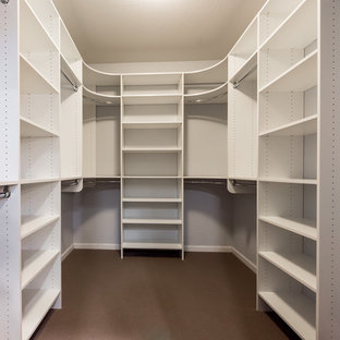 Photo of a large industrial walk-in wardrobe in Chicago with white cabinets and carpet.