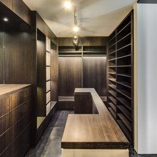 Imagen de vestidor unisex, urbano, extra grande, con armarios abiertos, puertas de armario de madera en tonos medios, suelo de cemento y suelo negro