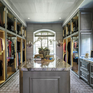 This is an example of a large transitional gender-neutral walk-in wardrobe in Dallas with raised-panel cabinets, grey cabinets and carpet.