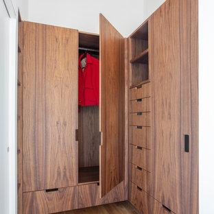 Imagen de armario vestidor unisex, minimalista, pequeño, con armarios con paneles lisos, puertas de armario de madera en tonos medios, suelo de madera clara y suelo marrón