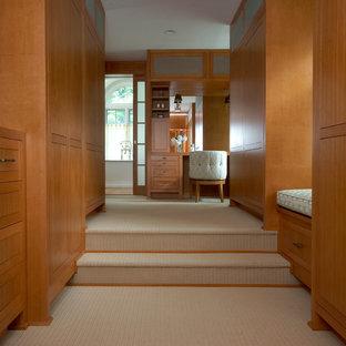 Modelo de vestidor unisex, minimalista, extra grande, con armarios con paneles lisos, puertas de armario de madera clara, moqueta y suelo beige