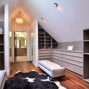Diseño de vestidor unisex, minimalista, de tamaño medio, con armarios con paneles lisos, puertas de armario con efecto envejecido y suelo de madera en tonos medios