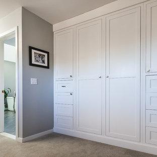 Ejemplo de armario de hombre, moderno, grande, con armarios estilo shaker, puertas de armario blancas, moqueta y suelo beige