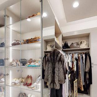 Ejemplo de armario y vestidor de mujer, moderno, grande, con armarios tipo vitrina, puertas de armario grises, moqueta y suelo gris
