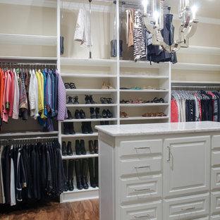 Imagen de armario vestidor unisex, mediterráneo, grande, con armarios abiertos, puertas de armario blancas, suelo de madera oscura y suelo marrón