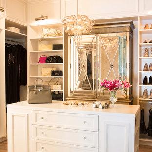 Diseño de armario vestidor de mujer, tradicional, grande, con puertas de armario blancas, suelo de madera en tonos medios y armarios con paneles empotrados