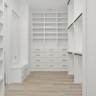 Diseño de armario vestidor unisex, campestre, grande, con armarios estilo shaker, puertas de armario blancas, suelo de baldosas de cerámica y suelo beige