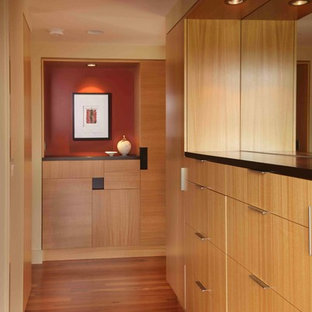 Large contemporary gender-neutral walk-in wardrobe in Portland with flat-panel cabinets, medium wood cabinets and medium hardwood floors.