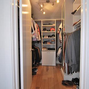 Immagine di una piccola cabina armadio per uomo moderna con ante lisce, ante bianche, pavimento in legno massello medio e pavimento multicolore