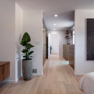 Esempio di un grande spazio per vestirsi unisex design con parquet chiaro, ante lisce, ante in legno scuro e pavimento beige