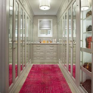 Aménagement d'un dressing classique pour une femme avec un placard avec porte à panneau encastré et des portes de placard grises.