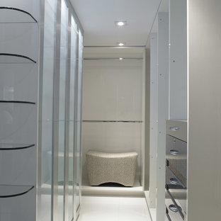 Modelo de armario vestidor de hombre, moderno, de tamaño medio, con armarios con paneles lisos, puertas de armario grises, suelo de baldosas de porcelana y suelo beige