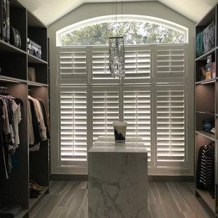 Modelo de armario y vestidor unisex y abovedado, moderno, con armarios abiertos, puertas de armario de madera en tonos medios, suelo de baldosas de porcelana y suelo gris