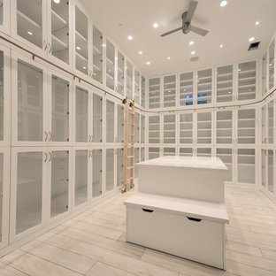 Idee per un grande spazio per vestirsi per donna design con ante di vetro, ante bianche e pavimento in gres porcellanato